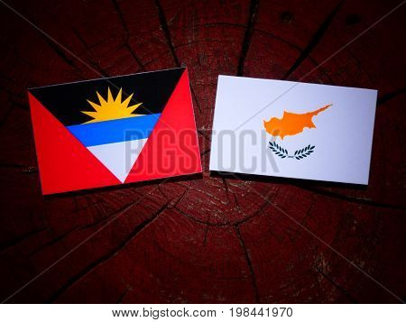 Antigua And Barbuda Flag With Cypriot Flag On A Tree Stump Isolated