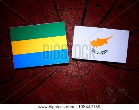 Gabon Flag With Cypriot Flag On A Tree Stump Isolated