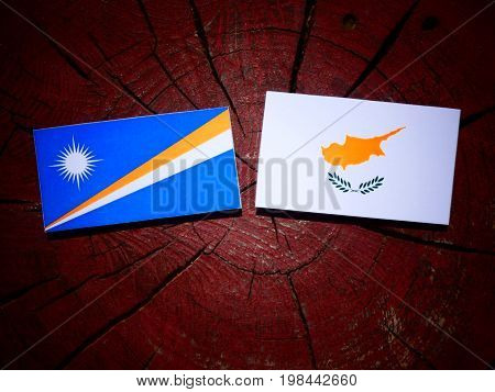 Marshall Islands Flag With Cypriot Flag On A Tree Stump Isolated