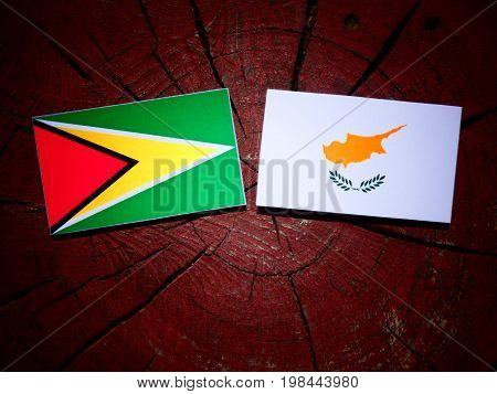 Guyana Flag With Cypriot Flag On A Tree Stump Isolated