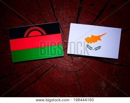Malawi Flag With Cypriot Flag On A Tree Stump Isolated
