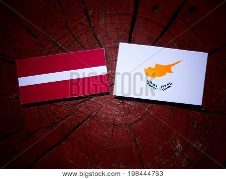 Latvia Flag With Cypriot Flag On A Tree Stump Isolated