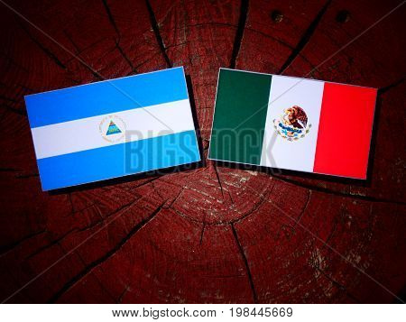 Nicaraguan Flag With Mexican Flag On A Tree Stump Isolated