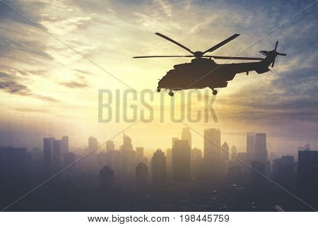 Picture of army helicopter flying over downtown shot at sunrise time