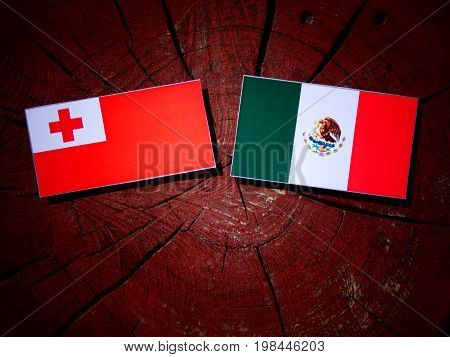Tongan Flag With Mexican Flag On A Tree Stump Isolated