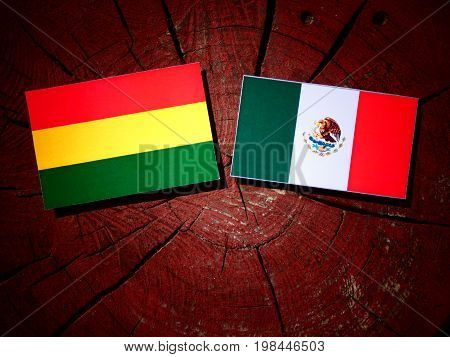 Bolivian Flag With Mexican Flag On A Tree Stump Isolated