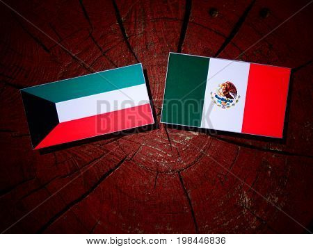Kuwaiti Flag With Mexican Flag On A Tree Stump Isolated