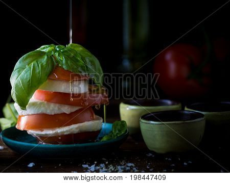 Fresh Caprese salad on a black background with olive oil drizzle