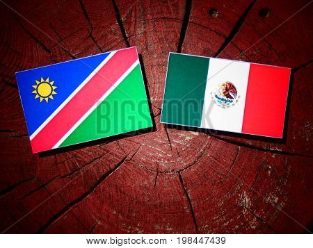 Namibian Flag With Mexican Flag On A Tree Stump Isolated