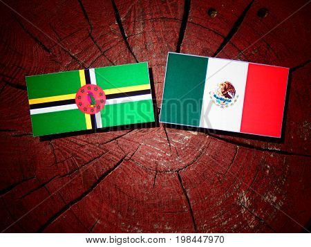 Dominica Flag With Mexican Flag On A Tree Stump Isolated