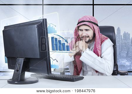 Picture of middle eastern male entrepreneur looking at a declining business graph on the monitor with winter background on the window