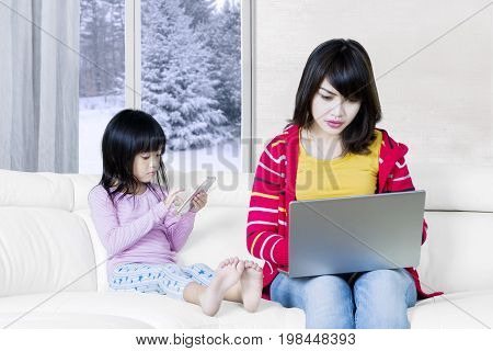 Photo of a busy mother sitting on the sofa while working with a laptop computer and her child playing mobile phone