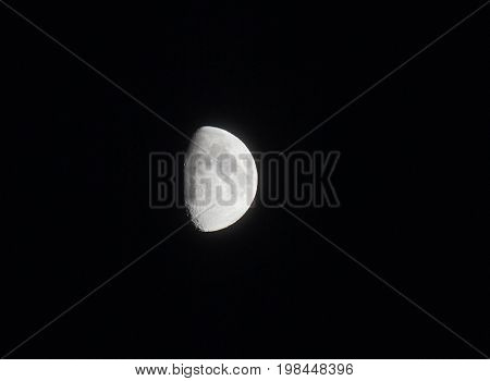 silver two thirds bright moon in a black sky showing seas and craters in shadow