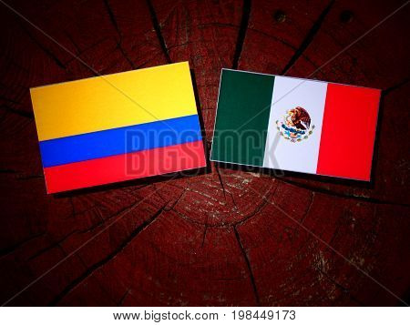 Colombian Flag With Mexican Flag On A Tree Stump Isolated