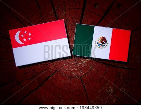 Singaporean Flag With Mexican Flag On A Tree Stump Isolated