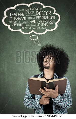 Young college student holding a book while thinking dream jobs with cloud speech over his head