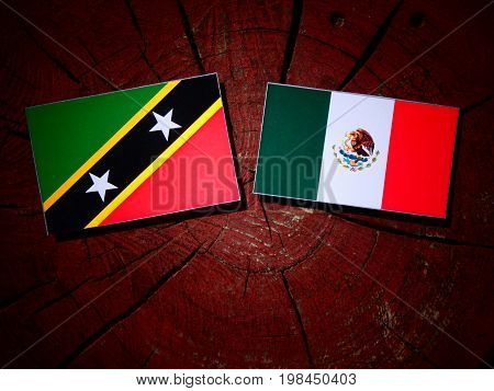 Saint Kitts And Nevis Flag With Mexican Flag On A Tree Stump Isolated