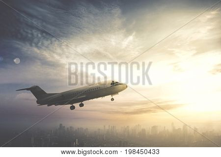 Image of commercial airplane flying over downtown shot at sunrise time