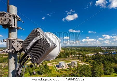 Part of telecommunication tower with outdoor unit of wireless communications system is including microwave antenna optic and power cables are located on the roof and city landscape as background. Outdoor unit of equipment of basic station.