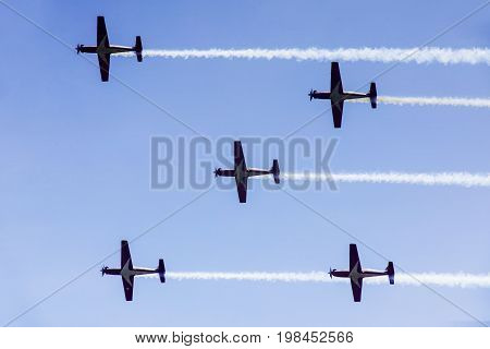 Picture of five jet planes flying in the blue sky while doing maneuvers