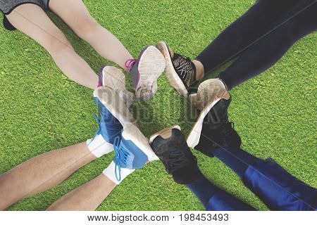Top view of group of friends sitting on the green grass make foot circle with their legs and different shoes after workout together