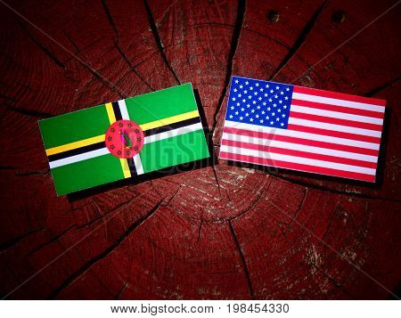 Dominica Flag With Usa Flag On A Tree Stump Isolated