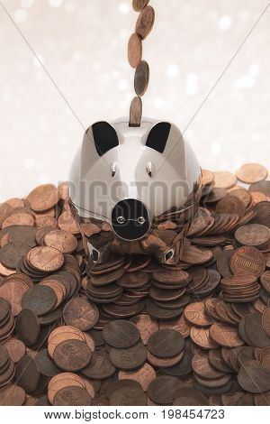 A chrome piggy bank on a pile of pennies with pennies coming down from above going into the coin slot.