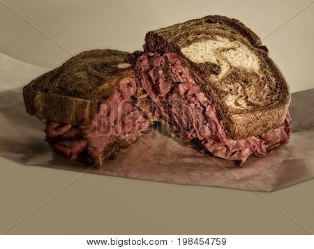 Two halves of a pastrami sandwich on rye bread with light background.