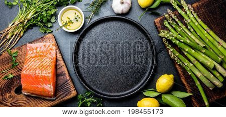 Raw Salmon Fillet, Asparagus, Lemons And Herbs Around Cast Iron Plate. Food Cooking Background With