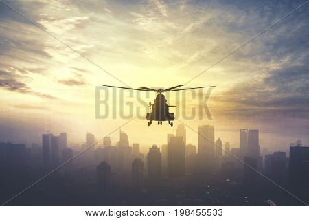 Silhouette of military helicopter hovering over downtown shot at sunset time