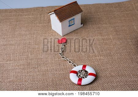 Model House And A Life Preserver With A Heart