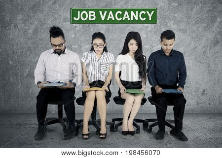 Group of multiracial employee candidates wait for job interview while sitting on office chair with their curriculum vitae resume