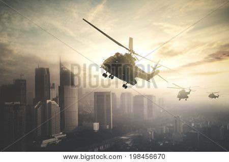 Silhouette of three army helicopters doing patrols while flying over downtown shot at sunset time