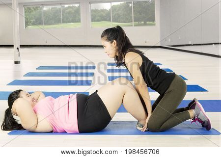 Female trainer helping fat woman doing sit up exercise in the fitness center