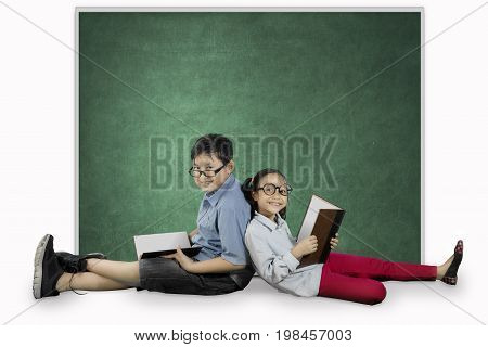 Picture of two elementary students looks happy while sitting near a blank chalkboard and holding a book in the studio