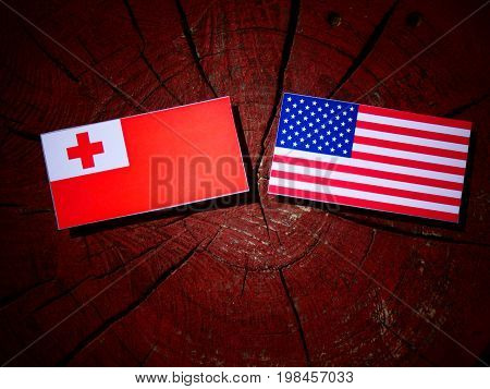 Tongan Flag With Usa Flag On A Tree Stump Isolated