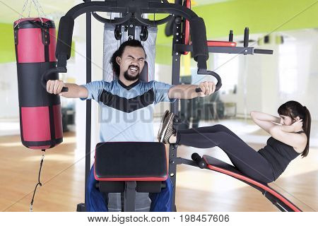 Young Afro man and Arabian woman workout on weights machine while pushing weights and doing sit-up