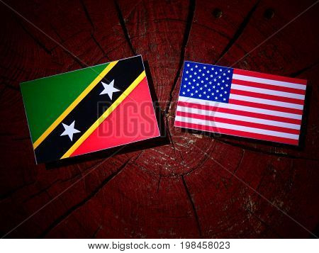 Saint Kitts And Nevis Flag With Usa Flag On A Tree Stump Isolated