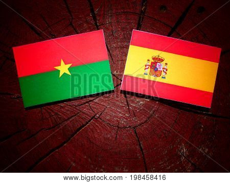 Burkina Faso Flag With Spanish Flag On A Tree Stump Isolated