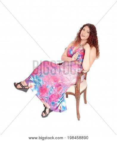 A lovely young woman in a long colorful dress sitting in an old fashion armchair with her legs crossed isolated for white background