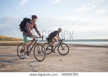 Twoo young male on a touring bicycle with backpacks and helmets  in the desert on a bicycle trip