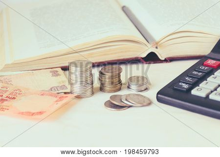 Money banknote coins in piles a calculator in front of an open book. The concept of expensive education and low scholarship. Toned image