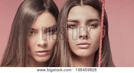 Beauty Photo Of Attractive Caucasian Twins Sisters Posing In Pink Interior.