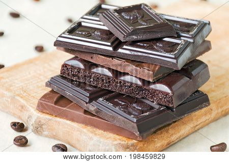 Broken chocolate bars of different kinds of chocolate are stacked on a wooden board around a bit of coffee beans