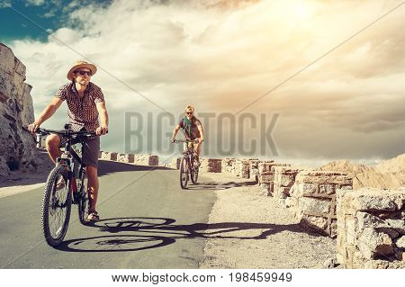 Two bicykle travelers on the mountain road in Himalaya