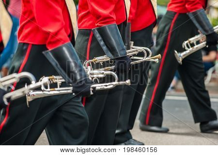 Trumpet players gloved hands in line on the marching band.