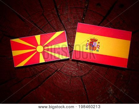 Macedonian Flag With Spanish Flag On A Tree Stump Isolated