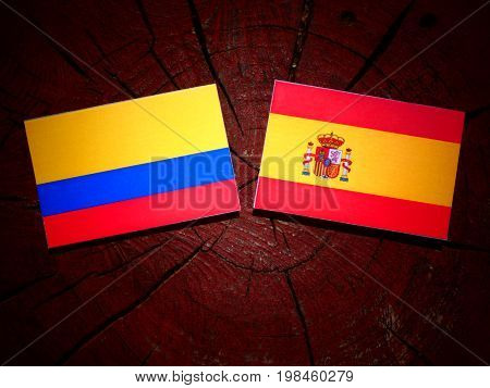Colombian Flag With Spanish Flag On A Tree Stump Isolated