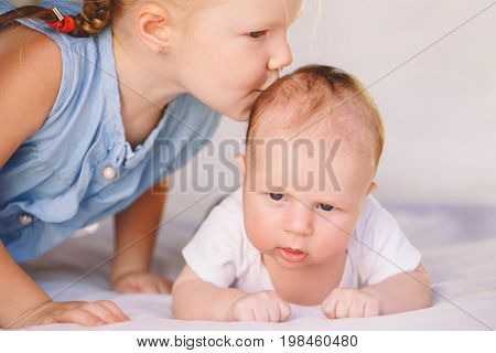 Lifestyle closeup portrait of cute white Caucasian girl sister kissing little baby lying on bed indoors. Older sibling with younger brother newborn. Family love bonding together concept.