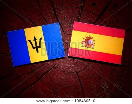 Barbados Flag With Spanish Flag On A Tree Stump Isolated